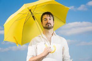 مردی زیر چتر برای دور بودن از افتاب سوختگی